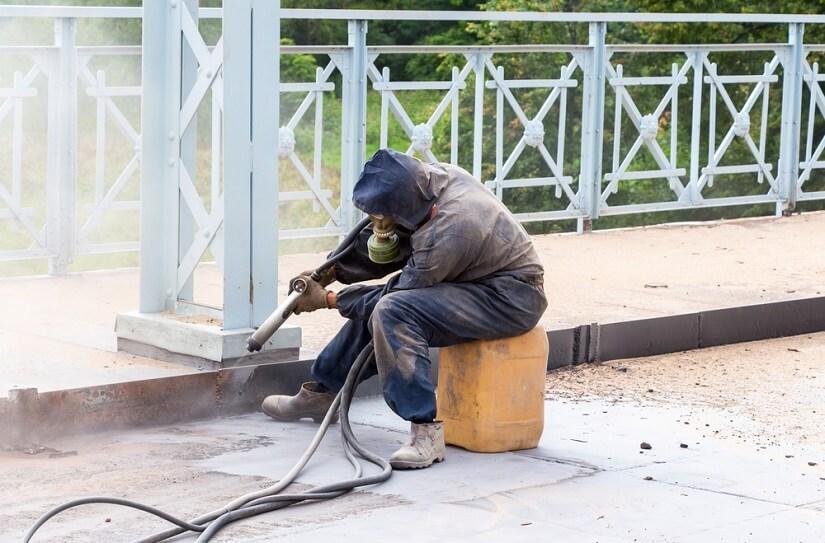 Arbeiter in Schutzkleidung reinigt eine Metallkonstruktion mit einem Sandstrahler