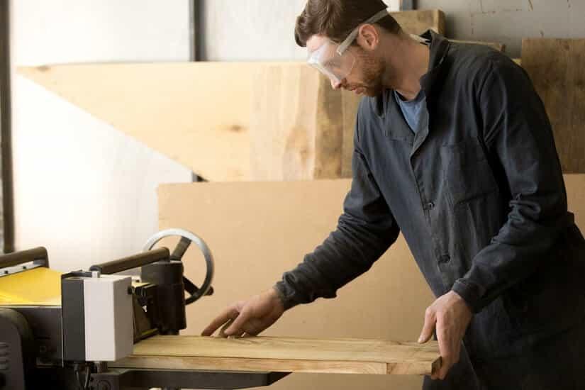 Schreiner arbeitet mit einer Dickenhobelmaschine
