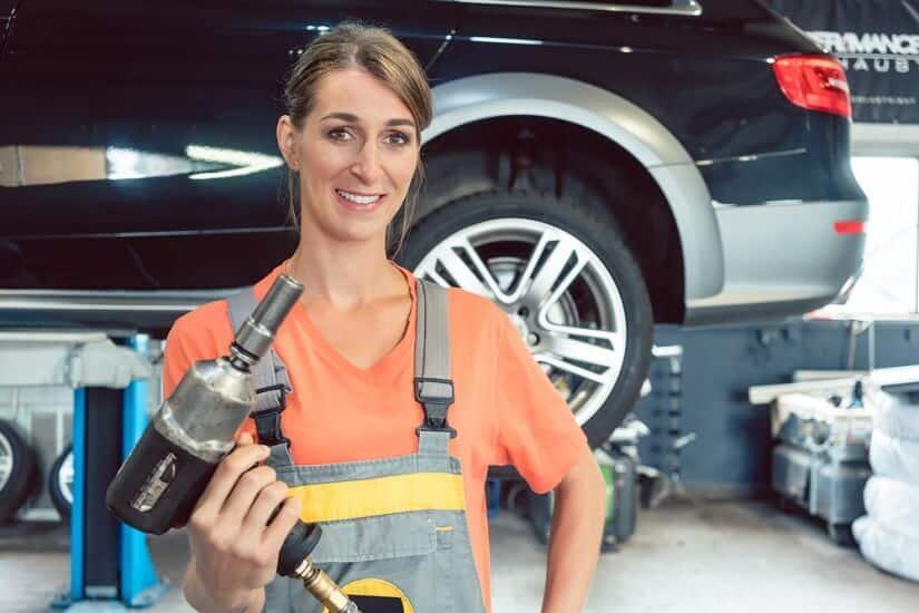 Eine Frau montiert Reifen mit einem Elektro-Schlagschrauben