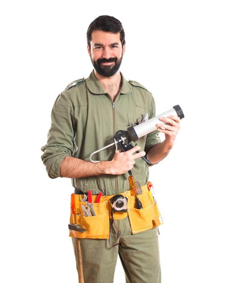 KFZ-Mechaniker hält Fettpresse in den Händen