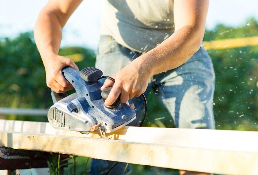 Mann arbeitet mit einer Hobelmaschine