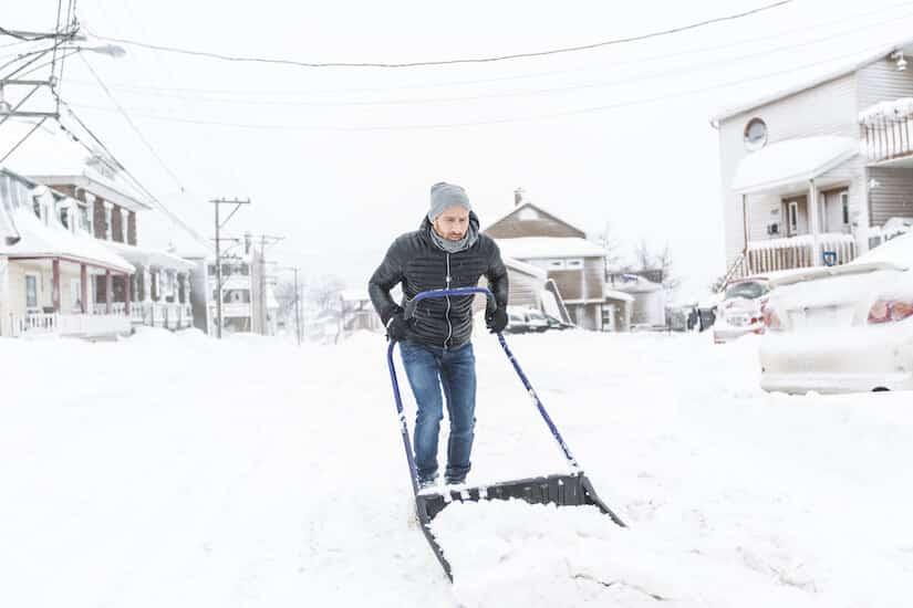 Mann räumt mit einer Schneewanne die Strasse