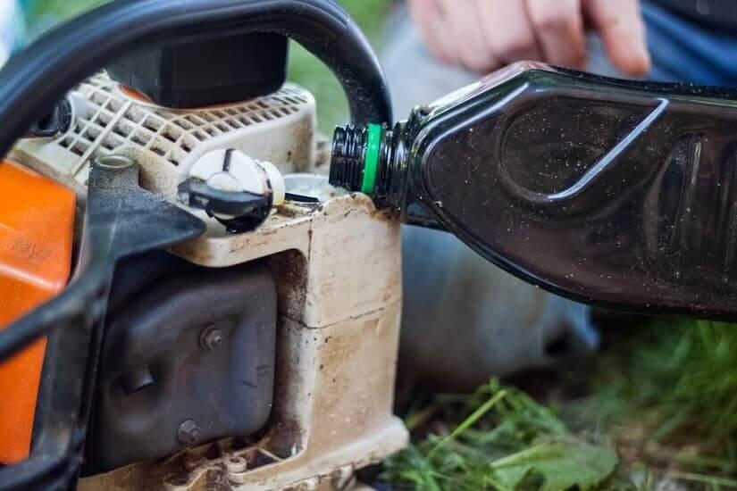 Eine Motorsäge wird mit Sägekettenöl befüllt