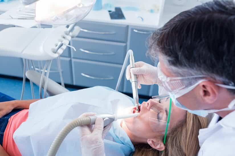 Zahnarzt nutzt einen Saugschlauch