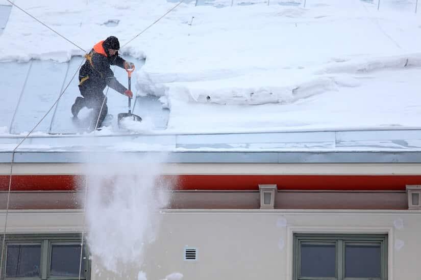 Schneeschaufel am Dach