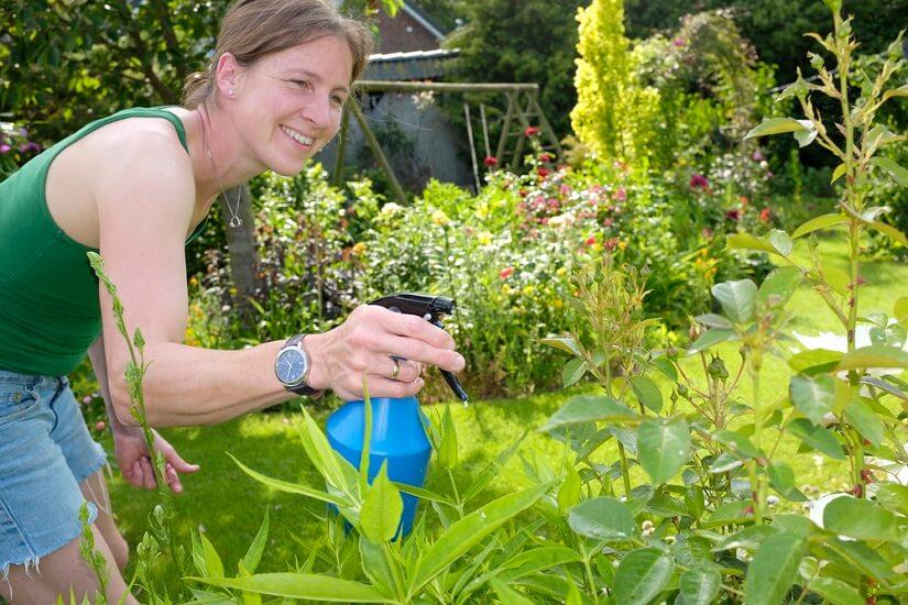 Frau mit Bio Spray gegen Ungeziefer im Garten