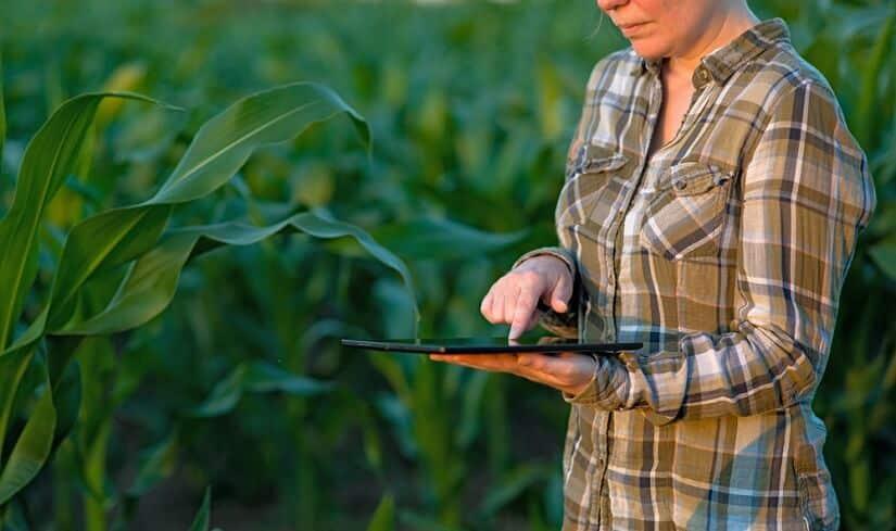Frau arbeitet auf den Feldern mit einem Bewässerungscomputer über Bluetooth an ihr Tablet angeschlossen