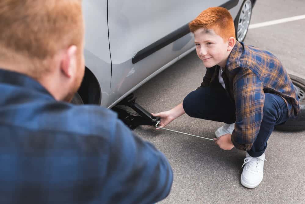 Kind wechselt Reifen mit einem Scherenwagenheber