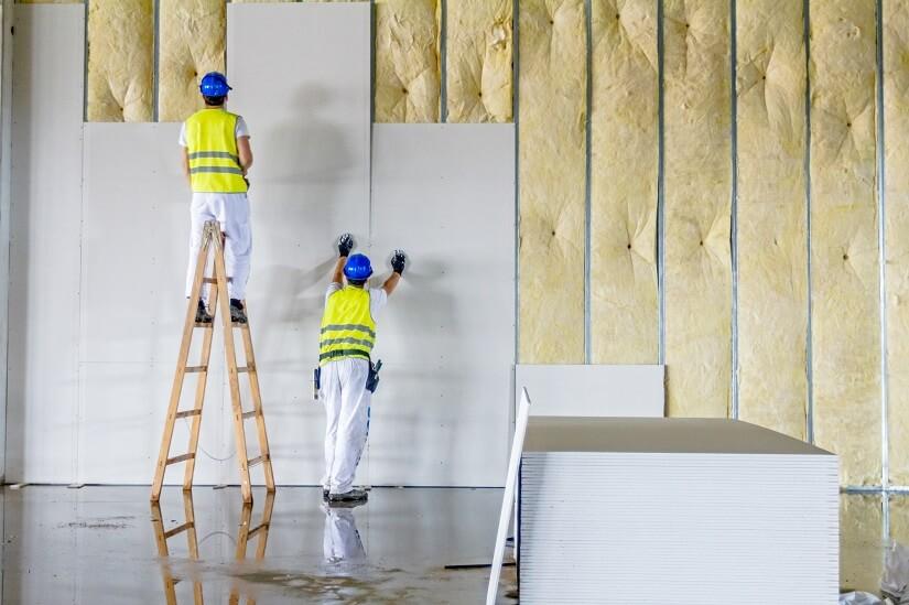 Handwerker bringen Dämmplatten innen gegen Schimmel an. | Foto: roman023 / Depositphotos.com