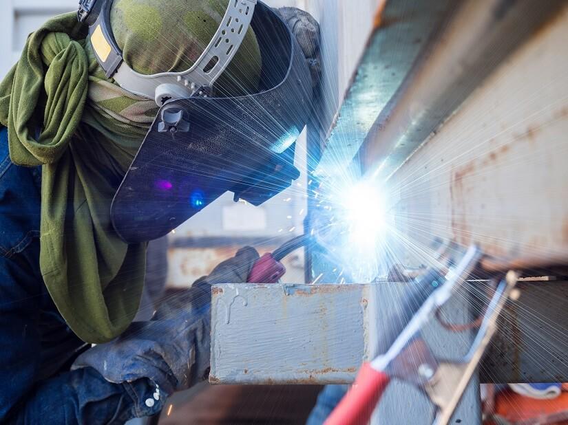 Mann arbeitet mit einem Schutzgas Schweißgerät im industriellen Bereich.