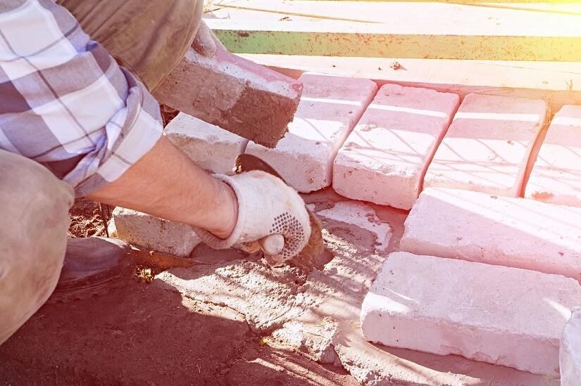 Heimwerker verlegt Steine auf Trasszementmörtel