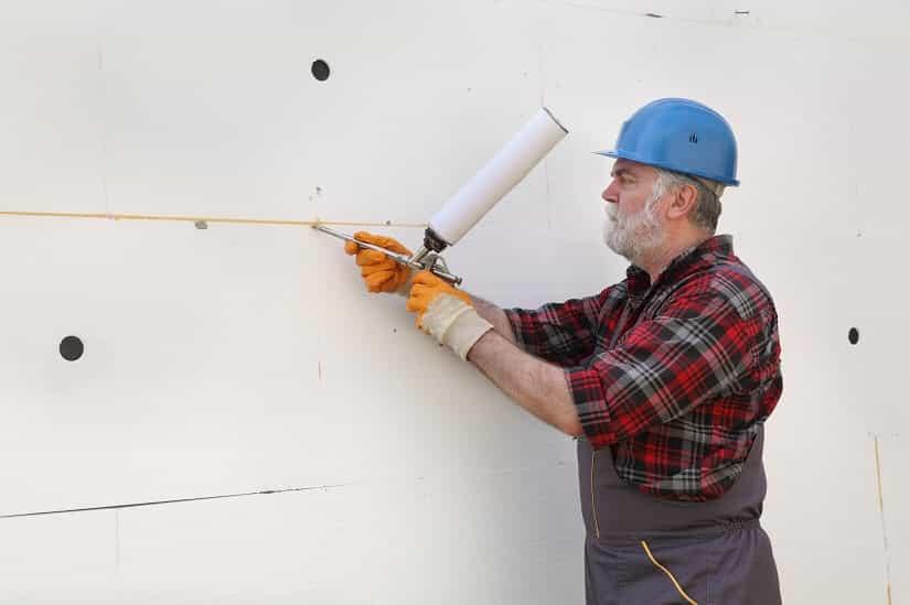 Handwerker versiegelt Isolierplatten mit einer Bauschaumpistole.