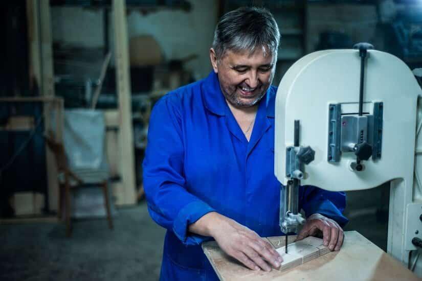 Werkstatt-Mitarbeiter bedient eine Ständerbohrmaschine