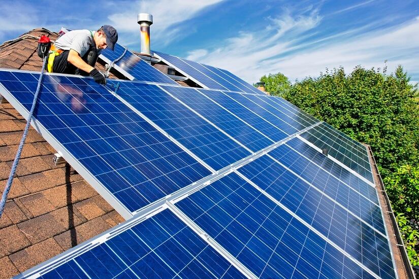 Techniker montiert die Solarmodule einer PV-Anlage