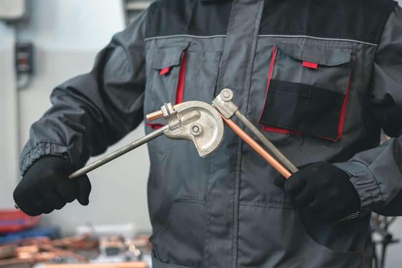 Handwerker biegt ein Kupferrohr