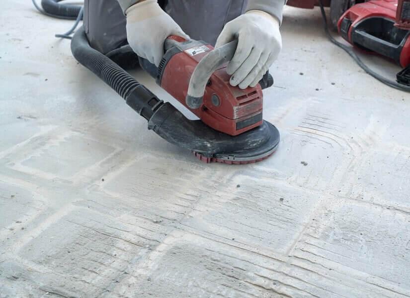 Handwerker beim Beton-Schleifen mit der Handschleifmaschine