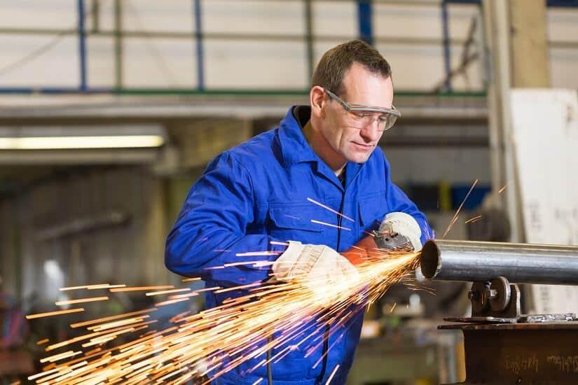 Stahlbauarbeiter schleift Metall mit einem Einhand Winkelschleifer