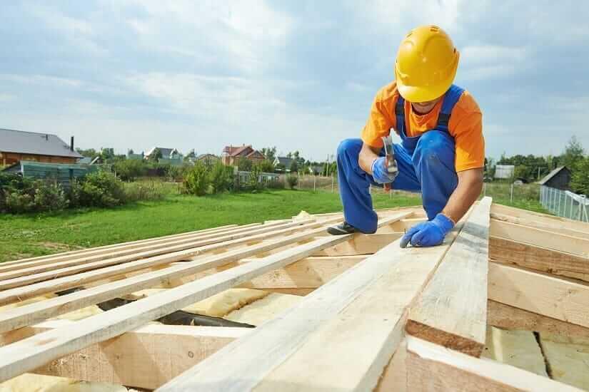 Zimmermann bei der Verwendung eines Zimmermannshammers mit Holzgriff an einem Dach