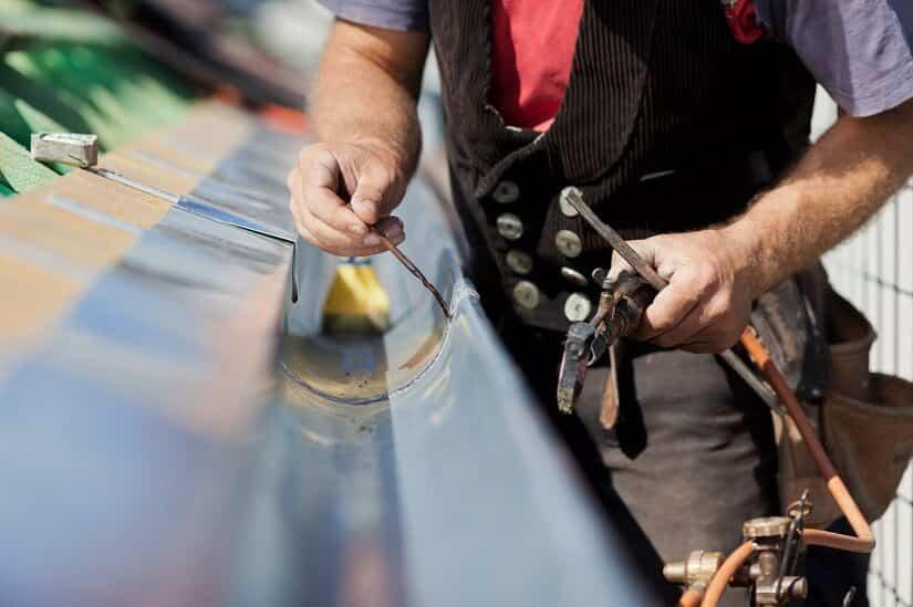 Ein Dachdecker dichtet eine Dachrinne ab