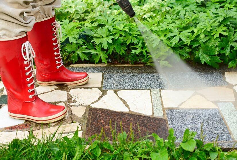Heimwerker reinigt Steinplatten eines Gartenpfads