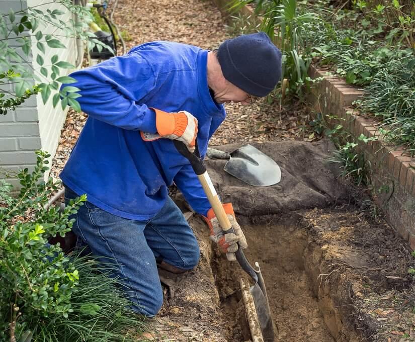 Ausgraben eines Grabens für die Verlegung eines Drainagerohrs